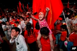 A child joins adult supporters of Myanmar's National League for Democracy party to celebrate as unofficial election results are posted outside the NLD headquarters in Yangon, Myanmar, Nov. 9, 2015.