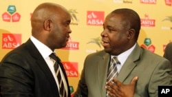 FILE - Kirsten Nematandani, president of the South African Football Association (R) shakes hands with then coach for South Africa's national soccer team Pitso Mosimane, in Johannesburg, South Africa, July 15, 2010.