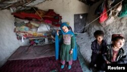 Afghan children stand inside a shelter at a refugee camp in Kabul May 31, 2016. Amnesty International says the number of internally displaced people in Afghanistan has doubled to 1.2 million since 2013.