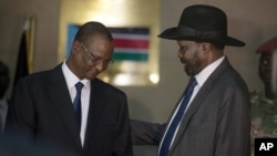 South Sudan's First Vice President Taban Deng Gai, left, speaks with President Salva Kiir after Taban was sworn in, replacing opposition leader Riek Machar, at the presidential palace in Juba, South Sudan, July 26, 2016.