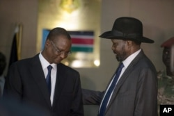 FILE - South Sudan's First Vice President Taban Deng Gai, left, speaks with President Salva Kiir, right, after Taban was sworn in, replacing opposition leader Riek Machar, at the presidential palace in Juba, South Sudan, Tuesday, July 26, 2016.