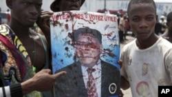 Wanachama wa upinzani UDPS wakishikilia picha za Etienne Tshisekedi zilizo na damu baada ya walinzi wa rais kufyatua risasi kwenye kundi la watu nje ya uwanja wa ndege wa Kinshasa,NDjili huko Kinshasa.