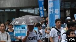 有香港市民帶同寫上標語的雨傘,冒著雷暴警告、大驟雨及超過攝氏30度的高溫天氣參與毅行爭普選活動 (美國之音湯惠芸拍攝)