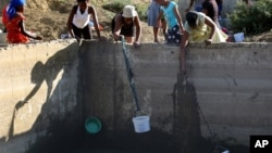 Women use buckets and cloth to collect stagnant rain water from an unfinished sewerage treatment tank, now used as a well, to do their laundry in Senekal, South Africa where taps and water sources have run dry, Jan. 7, 2016.