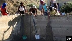 Người dân sử dụng xô và vải để lấy nước mưa đọng từ một bể xử lý nước thải ở Senekal, Nam Phi, ngày 7/1/2016.