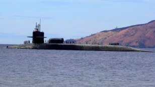 FILE - A U.S. Navy crew stands on the USS Michigan, an Ohio-class guided-missile submarine, as it prepares to dock at Subic Freeport, a former US naval base west of Manila, Philippines, March 25, 2014. The sub was on a routine port call.