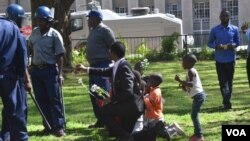 FILE: Vendors leader Sten Zvorwadza and some children attempt to give police flowers and cakes as a sign of love.