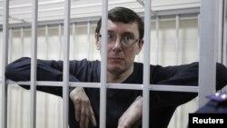 Mantan Mendagri Ukraina Yuriy Lutsenko menatap keluar dari dalam selnya saat berlangsung persidangannya di Kiev, Februari lalu.
