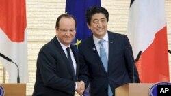 Presiden Perancis Francois Hollande (kiri) dan PM Jepang Shinzo Abe berjabat tangan seusai jumpa pers di rumah dinas PM Abe di Tokyo (7/6).