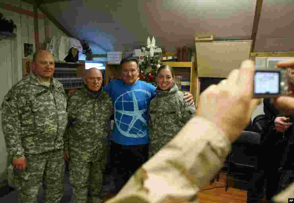 U.S. comedian Robin Williams, third from left, poses for photographs with U.S. soldiers at a U.S. base in Kabul, Afghanistan, Dec. 20, 2007.