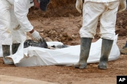 Forensic experts examine human remains at a mass grave in the village of Tomasica, near the Bosnian town of Prijedor, Oct. 31, 2013. Exhumations are currently underway at Koricani Cliffs, a nearby site.