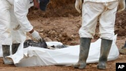Forensic experts examine human remains at a mass grave in the village of Tomasica, near the Bosnian town of Prijedor, Oct. 31, 2013.