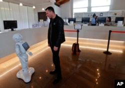 FILE - A guest from Moldavia asks robot Robby Pepper for information at the front desk of hotel in Peschiera del Garda, northern Italy, March 12, 2018. The hotel uses the robot to assist guests.