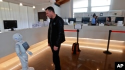In this photo dated March 12, 2018, Mihail Slanina, a guest from Moldavia, asks robot Robby Pepper for information at the front desk of hotel in Peschiera del Garda, northern Italy. The hotel uses the robot to assist guests. (AP Photo/Luca Bruno)