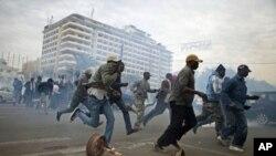2月15日达喀尔的反政府抗议者躲避催泪弹瓦斯