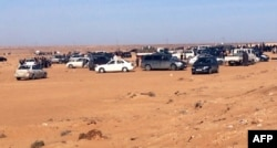 FILE - Displaced Libyans from the western city of Tawergha wait by their cars to enter the city, which lies about 250 kilometres east of the capital Tripoli, on Feb. 1, 2018.