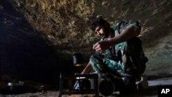 一名敘利亞反政府戰士在一個據點山洞內休息(資料圖片)