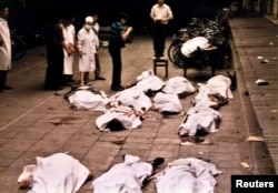 FILE - Medical workers of Beijing's Fuxingmen Hospital look at bodies of protesters killed by soldiers near Tiananmen Square on June 4, 1989.
