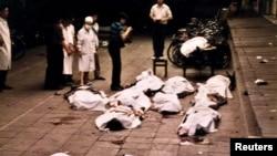 资料照片:在天安门广场附近,北京复兴门医院的医务工作者看着被军队打死的抗议者的遗体。(1989年6月4日)