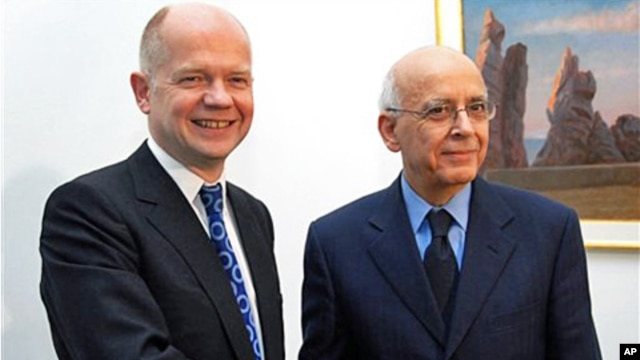 Tunisian Prime Minister Mohamed Ghannouchi, right, shakes hands with Britain's Foreign Secretary William Hague during a meeting at Carthage Palace, outside Tunis, February 8, 2011