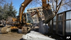 Bulldozers tear down a concrete wall erected in the northern city of Mitrovica on Sunday, Jan. 5, 2017, that has provoked tensions between Kosovo and neighboring Serbia.