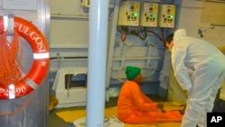 Seorang anggota Angkatan Laut Italia membantu seorang migran yang baru saja diselamatkan dekat pulau Lampedusa (25/10).