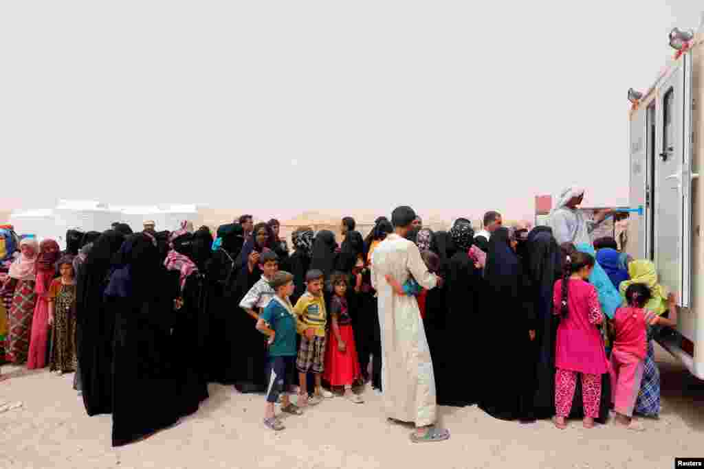 Displaced people, who fled from Falluja because of Islamic State violence, stand in line for treatment at a refugee camp in Ameriyat Falluja, south of Falluja, Iraq.