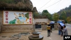 2016年10月22日,在中國陝西省梁家河,中國國家主席習近平青年時期生活過的窯洞外面有一幅描繪青年習近平指引方向的壁畫。