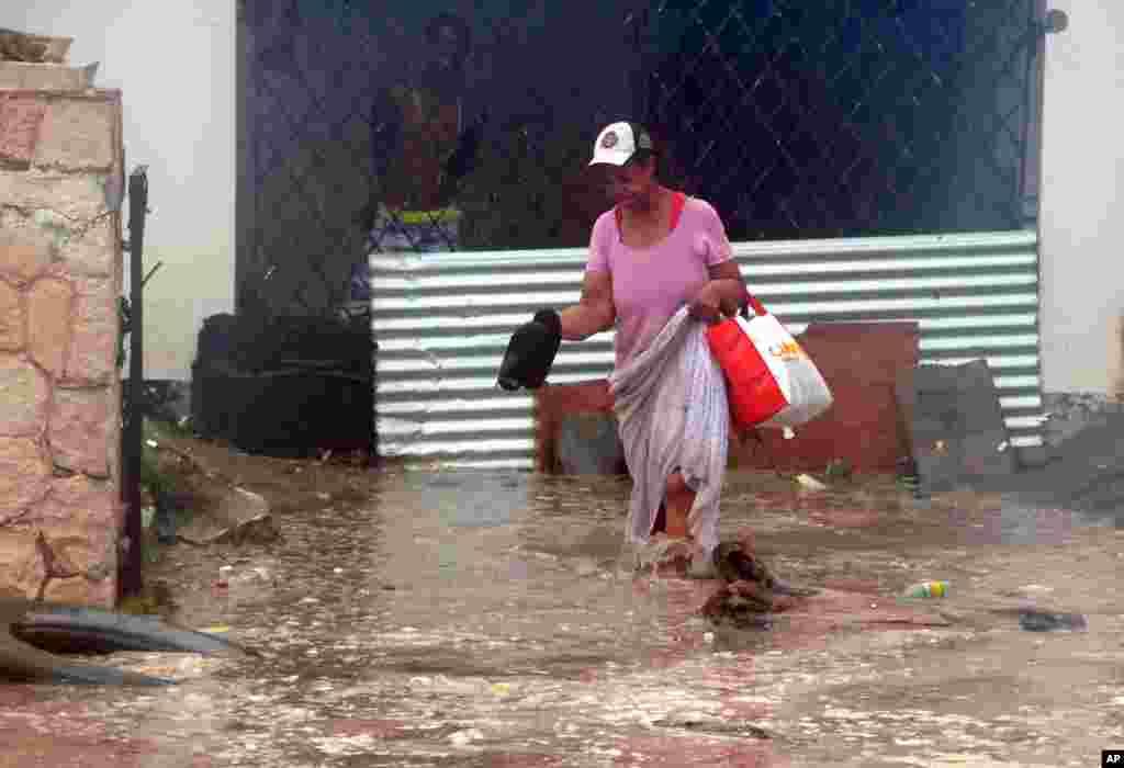 Une femme pataugeant dans les eaux d'inondation alors qu'elle tente de quitter sa maison dans l'est de Kingston, en Jamaïque