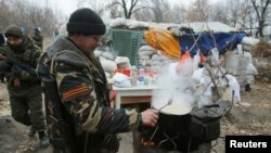 A pro-Russian separatist cooks food next to a checkpoint in the Spartak area near the Sergey Prokofiev International Airport in Donetsk, Nov. 18, 2014. (REUTERS/Antonio Bronic)