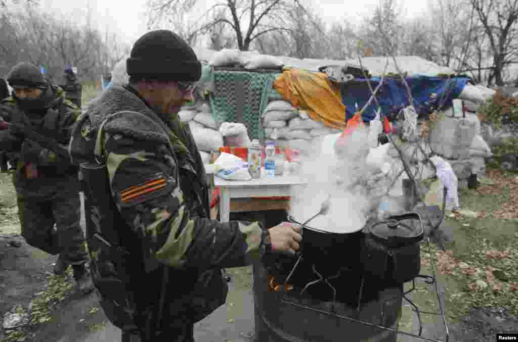 A pro-Russian separatist cooks food next to a checkpoint in the Spartak area near the Sergey Prokofiev International Airport in Donetsk, Nov. 18, 2014.
