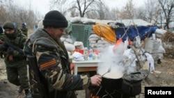 Phiến quân đòi ly khai thân Nga nấu thức ăn bên cạnh một trạm kiểm soát ở Donetsk, ngày 18/11/2014.