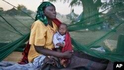 Sur cette photo prise le jeudi 2 janvier 2014 , une mère déplacée et son bébé , l'une des rares à avoir une moustiquaire , se réveiller le matin, après avoir dormi à la belle étoile, quelques-uns des milliers de personnes qui ont fui les récents combats entre forces gouvernementales et rebelles à Bor en bateau sur le Nil Blanc , dans la ville de Awerial , le Sud-Soudan . ( AP Photo / Ben Curtis )