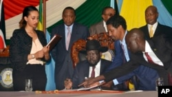 South Sudan President Salva Kiir, seated, signs a peace deal as Kenya's President Uhuru Kenyatta, center-left, Ethiopia's Prime Minister Hailemariam Desalegn, center-right, and Uganda's President Yoweri Museveni, right, look on in Juba, South Sudan.