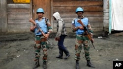 FILE - Two MONUSCO UN soldiers stand guard in Goma's port, eastern Congo.