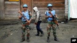 Deux soldats de la mission des Nations unies au Congo patrouillent à côté d'un passant à Goma, RDC.