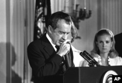 FILE - Richard Nixon performs the last acts of his presidency in the White House East Room, August 9, 1974, as he bids farewell to his Cabinet, aides, and staff.