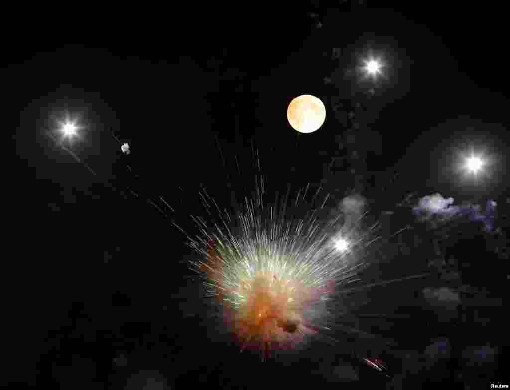 In this photo released Aug. 14, fireworks explode in front of the supermoon outside the town of Mosta, celebrating the feast of its patron saint, in central Malta, Aug. 10, 2014.