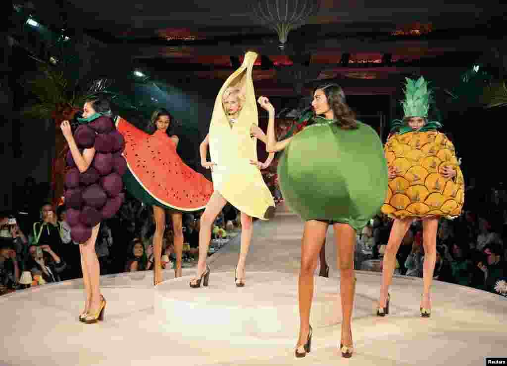 Para model mengenakan kreasi busana yang berbentuk buah-buahan pada London Fashion Week di London, Inggris.