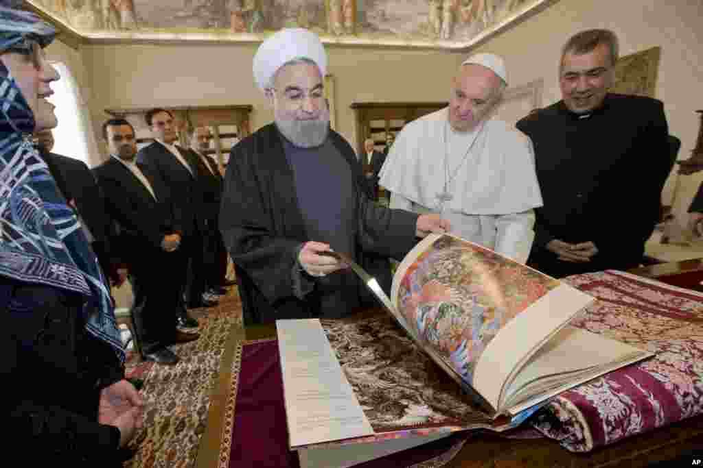 Iranian President Hassan Rouhani, left, leafs through a book he gave to Pope Francis as a gift, during their private audience at the Vatican.