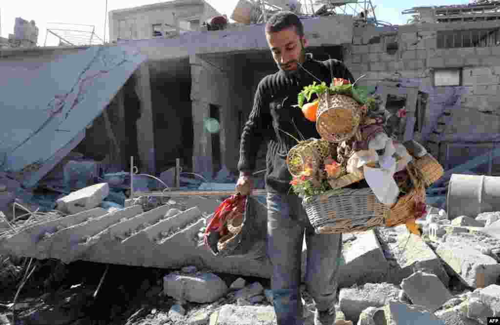 A Syrian man salvages belongings from a destroyed house following air strikes by regime forces in the town of Ras al-Ain near the border with Turkey, November 16, 2012.