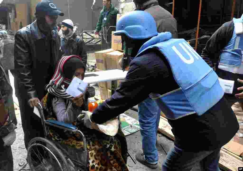 This photo released by the Syrian official news agency SANA shows a U.N. relief worker giving food supplies to a Palestinian woman in a wheelchair at the gate of the besieged Yarmouk refugee camp on the southern edge of Damascus, Feb. 4, 2014.