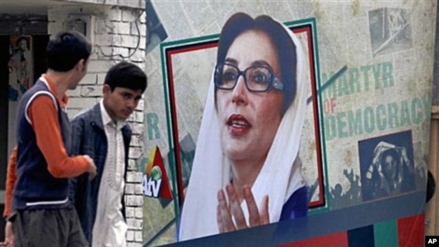 Pakistan youths walk past a portrait of former prime minister Benazir Bhutto displayed at the site where she was assassinated in Rawalpindi (File)