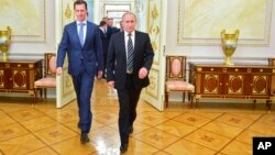 In this photo taken on Tuesday, Oct. 20, 2015, Russian President Vladimir Putin, right, and Syria President Bashar Assad arrive for their meeting in the Kremlin in Moscow, Russia.