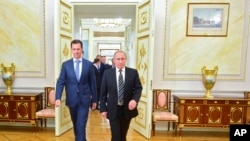 Russian President Vladimir Putin, right, and Syria President Bashar Assad arrive for their meeting in the Kremlin, Moscow, Oct. 20, 2015.
