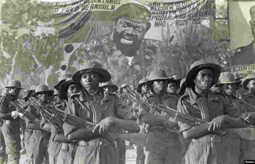 Guerrilheiros da UNITA marcham na frente da imagem de Jonas Savimbi