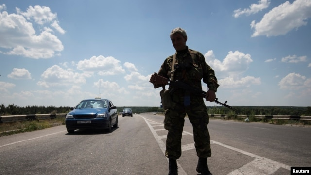 An armed pro-Russian separatist stands guard at a road check point outside the eastern Ukrainian city of Luhansk, June 8, 2014.