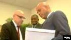 Prezidan Martelly ki tap resevwa rapò a nan men kowòdonatè komisyon an, Doktè Réginald Boulos. (Foto: HPN/Clarens Renois--9 desanm 2014).