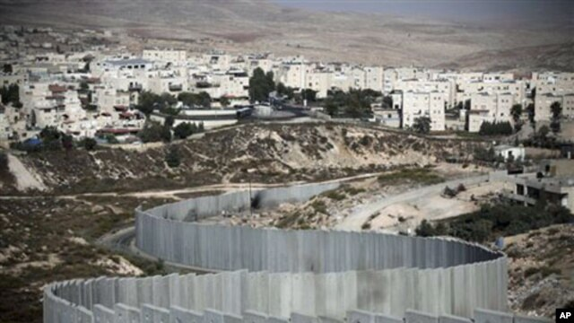 The East Jerusalem neighborhood of Pisgat Zeev is seen behind a section of Israel's separation barrier, 15 Oct 2010