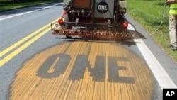 国际反贫困公益组织(ONE)成员格雷格将组织标识 - ONE - 喷洒在77号公路引起人们对贫困的认识